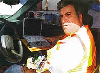 A foreman enters daily job data on a laptop computer instead of filling out paper forms as part of a new field reporting system.