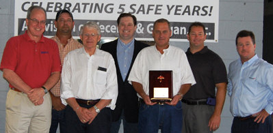 """Sharpe Bros. VP Ivan Clayton holds a plaque from Steve Beals with Travelers, far right, marking five years with no """"lost time"""" incidents. Also shown are Vecellio Group VP Safety John West, Sharpe Division Safety Manager John Riley Jr., Vecellio & Grogan President Bill Medcalf, Vecellio Group VP Michael Vecellio and VP Safety Mark Ligon. (Photo by Gloria Fields)"""