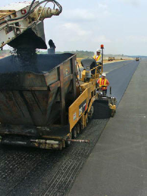 Paver Operator Angel Garcia, Screed Operator Alex Esquivel and the rest of the paving crew work on the airport runway and shoulder.