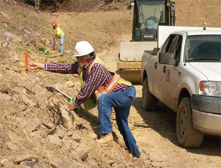 Foreman David Holly and Roller Operator Tonja Chandler check measurements in an area of fill. (Photo by Carl Thiemann)
