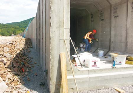 Junior Alkires spreads sealant between segments of a box culvert, which will be covered with backfill to bring the area up to grade. (Photo by Carl Thiemann)