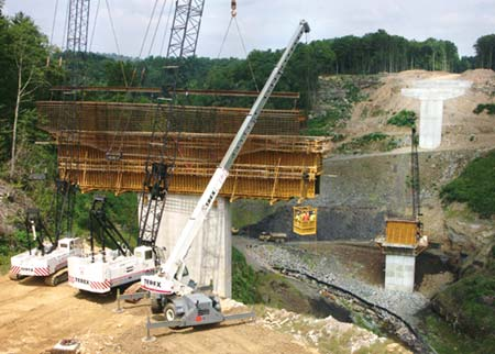 A crew of steel workers is lifted out to a bridge pier as Crane Operators Tommy Coiner and Richard Clary hold a rebar cage ready for placement on Vecellio & Grogan's East Beckley Bypass project. The crew will guide the cage into a waiting form, into which concrete will be poured to form a pier cap. (Photo by Carl Thiemann)