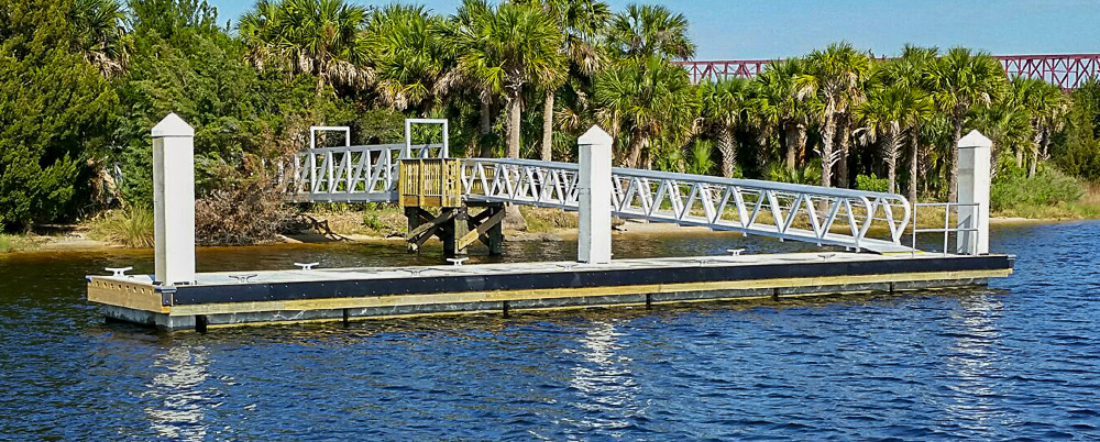 a floating dock with three pillars and a bridge leading to land covered in palm trees