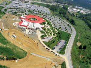 aerial view of a parking lot construction around a circular building with red pointed roof sections around the circle