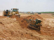 earth moving machinery prepares a field for construction