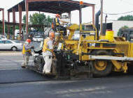 workers operating a machine laying down asphalt