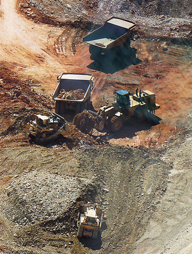 aerial view of front loaders transferring material into dump trucks
