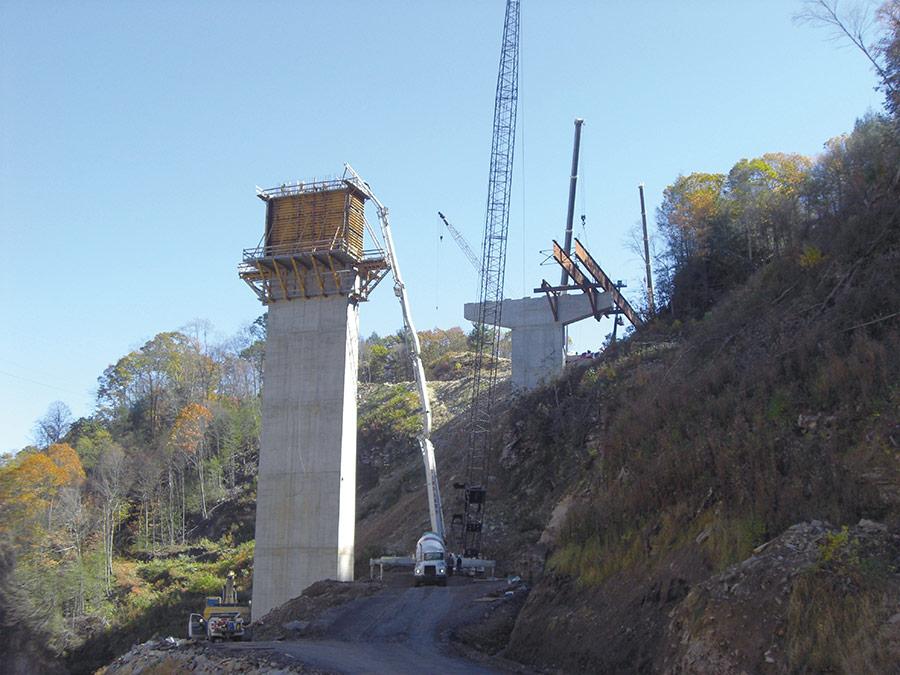 a cement truck pumps concrete up to a form for a bridge pylon