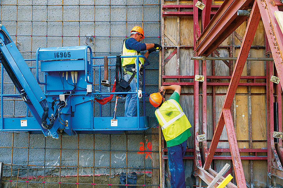 two workers assemble a wood and steel form for concrete to be poured into