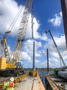 a crane lowers a section of pole at the end of a pier